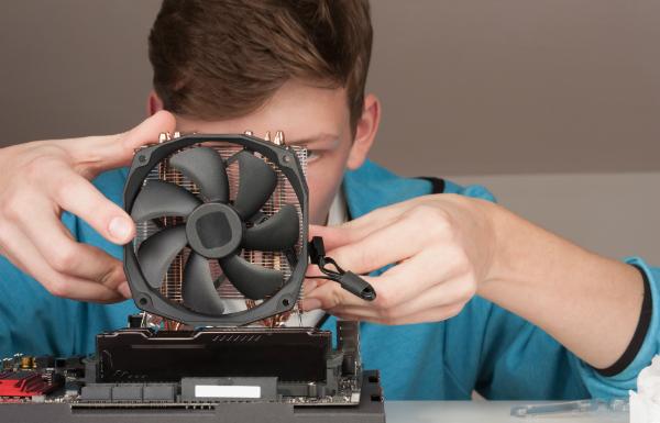Junger Mann installiert CPU-Kuehler-Ventilator auf Gaming-Motherboard