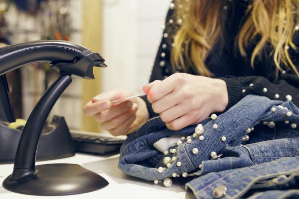 Frau scannt Barcode einer Jeansjacke