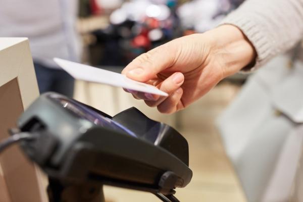 Kunde bezahlt mit NFC Kreditkarte am Kartenterminal Kasse im Einkaufszentrum